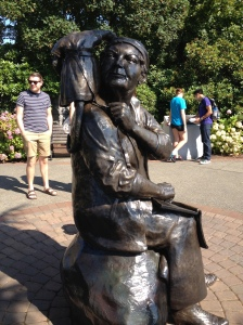 A statue of Emily Carr that makes her look like an unattractive man...that is a monkey on her shoulder.